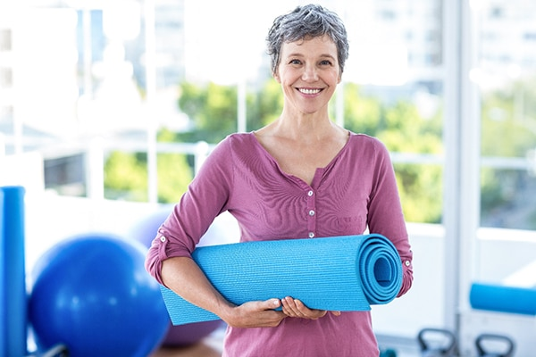 A woman in her 40s or 50s standing in a yoga studio holding a yoga mat.