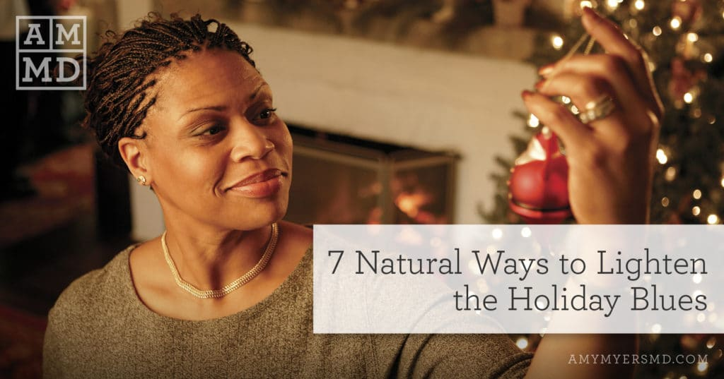 7 Natural Ways to Lighten the Holiday Blues - A Woman Holding a Christmas Ornament - Featured Image - Amy Myers MD