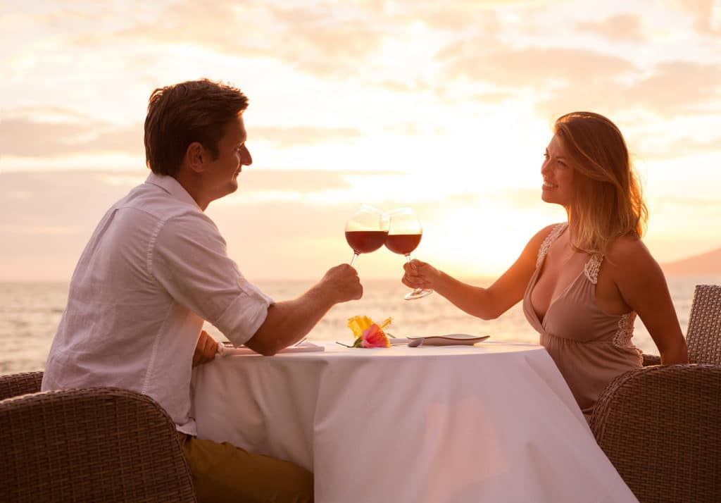 A couple toasting with wine glasses at a restaurant table overlooking an ocean sunset.