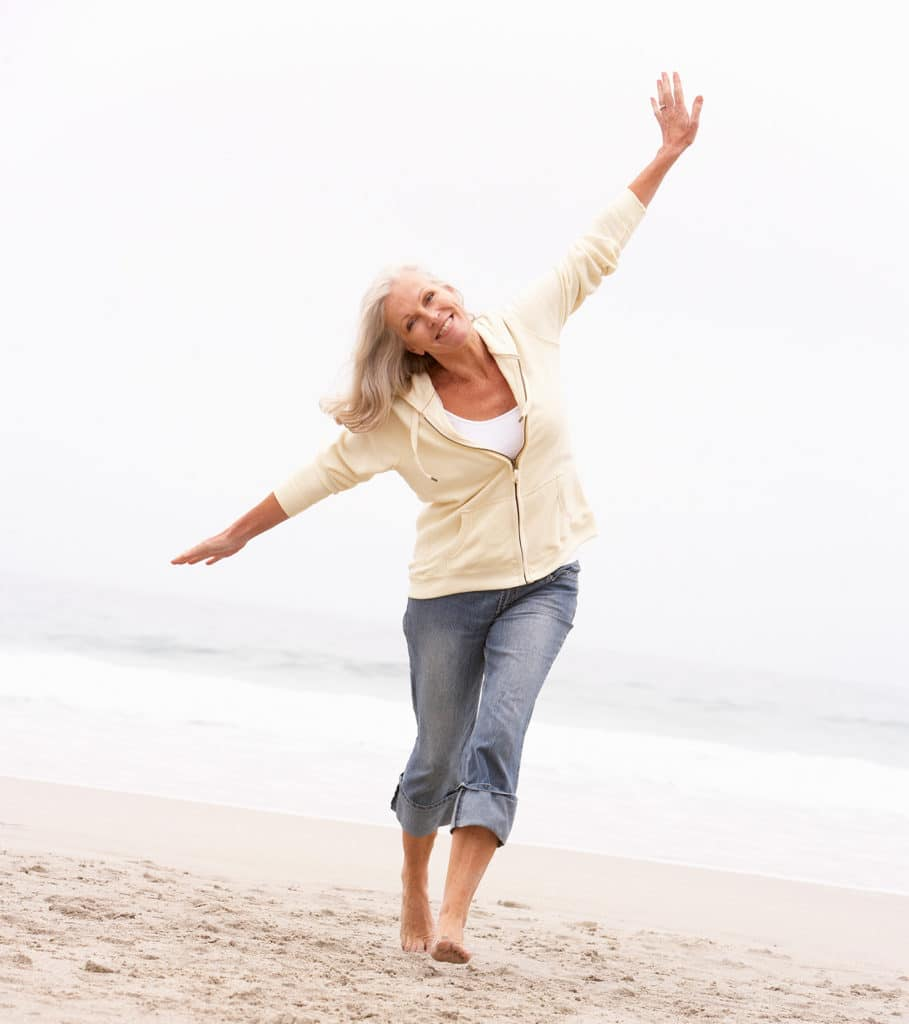 Woman in her 60s on a beach by the ocean enjoying life