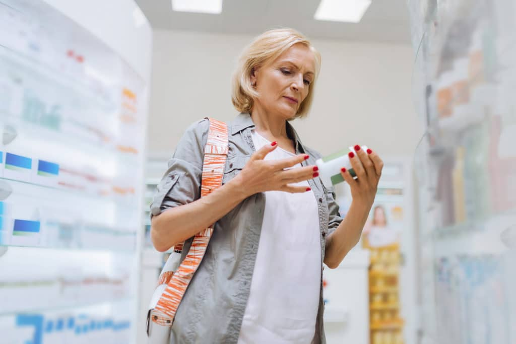 A woman in her 50s looking at a vitamin bottle in the among a multitude of options in the supplement isle of her local drug store.