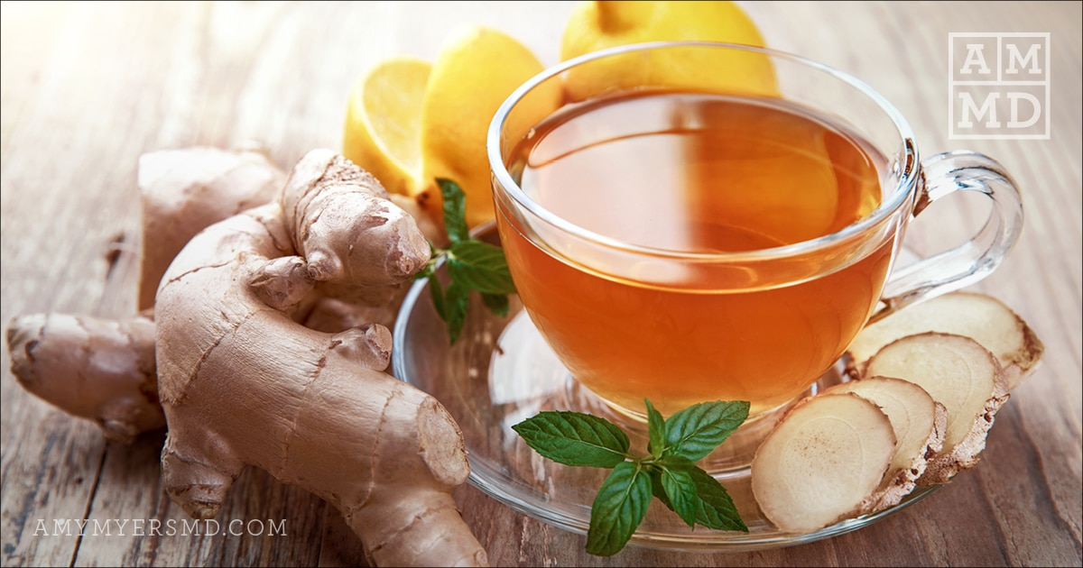 Cup of tea surrounded by ginger root and mint