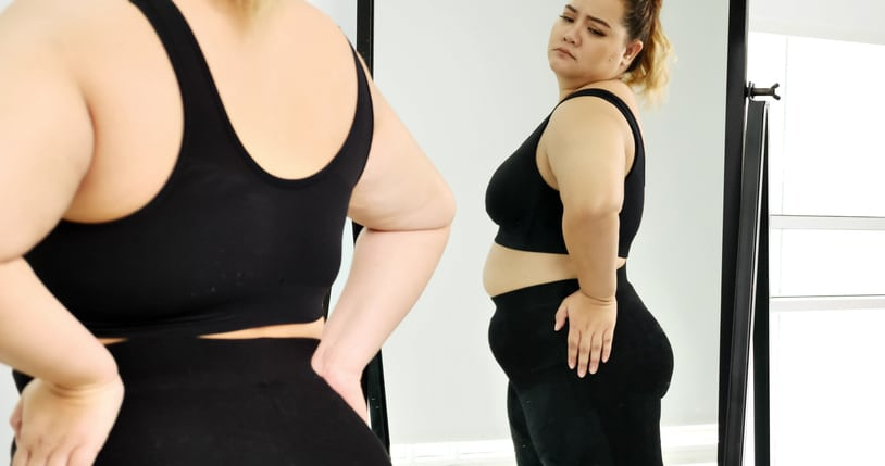 woman standing and looking at her stomach in a mirror